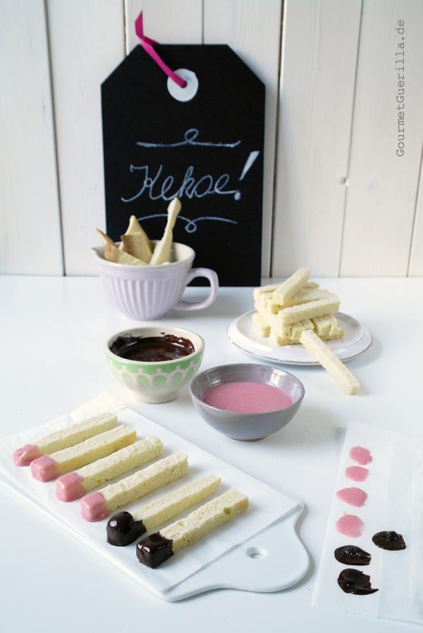 Kekse in Streichholzform werden mit rosa und braunem Guss verziert.