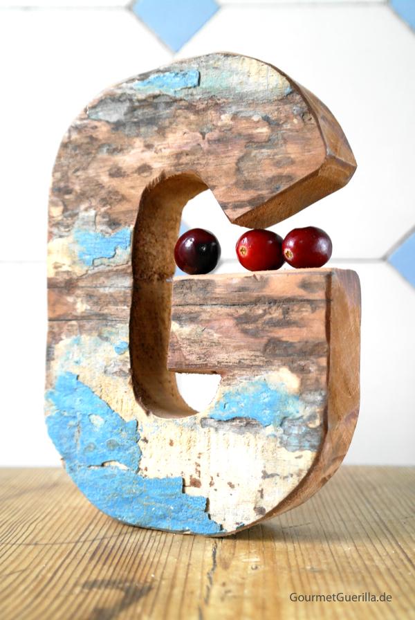 Drei Cranberries liegen auf einem Holzobjekt