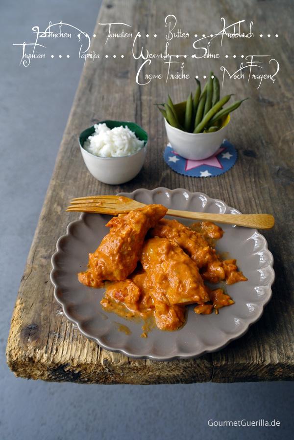 Huhn in provenzalischer Tomatensoße auf einem grauen Teller mit gewelltem Rand